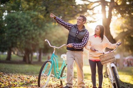 Smiling couple with bicycles at park on sunny day Stock Photo