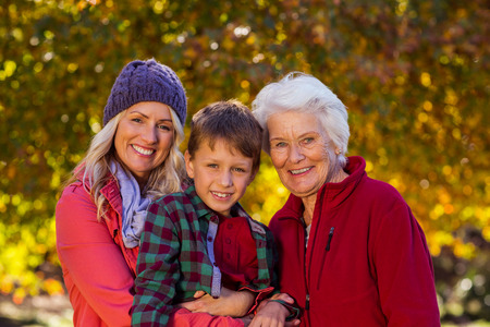 Portrait of boy with mother and grandmother at park during autumn