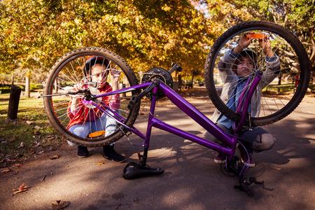 siblings: Siblings repairing bicycle in park