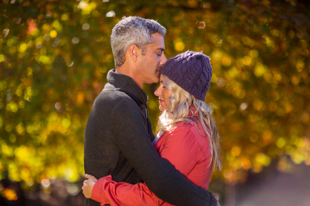 Side view of couple hugging at park during autumn