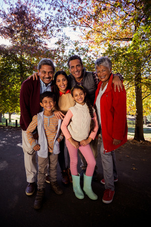 multigeneration: Full length of smiling multi-generation family standing at park during autumn Stock Photo