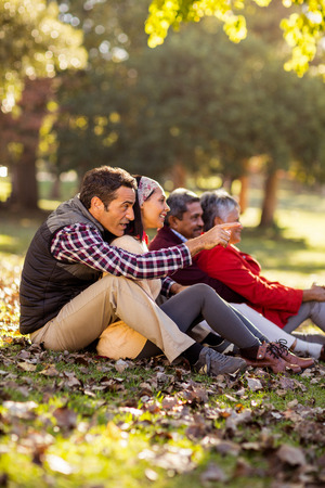 Happy family sitting against tree at park