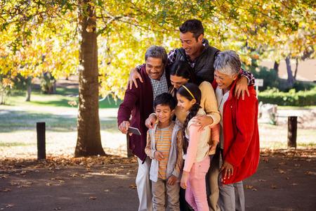 Happy multi-generation family taking selfie at park