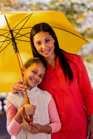 Portrait of mother and daughter with umbrella at park Stock Photo