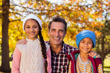Portrait of happy father with son and daughter at park during autumn