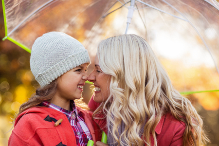 rubbing noses: Happy mother and daughter rubbing noses while holding umbrella at park Stock Photo
