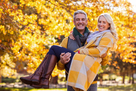man carrying woman: Portrait of happy man carrying woman at park during autumn Stock Photo