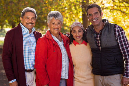 adult offspring: Portrait of happy two generation family at park Stock Photo