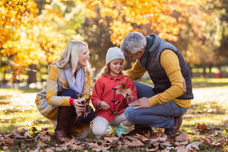 crouching: Happy family crouching against trees at park during autumn