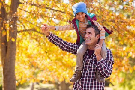 shoulder carrying: Cheerful father carrying son on shoulder against autumn tree at park