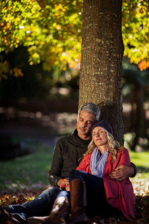 Mature couple relaxing under tree at park during autumn