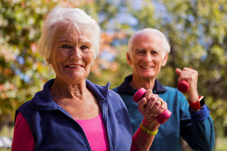 hand weight: Elderly couple making fitness and lifting hand weight in the park Stock Photo