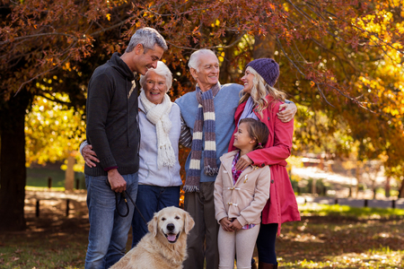 Multi-generation family standing with dog at park during autumn Stock Photo