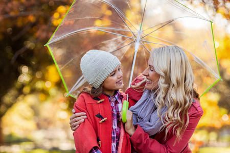 Happy mother and daughter holding umbrella while looking each other at park Stock Photo
