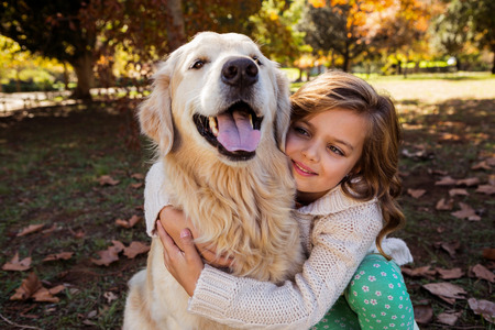 look after: Little girl embracing her dog in a park