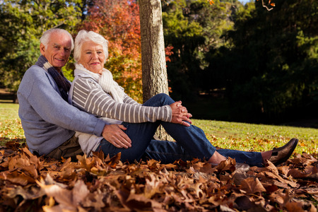 Senior couple sitting on the ground in a park Stock Photo