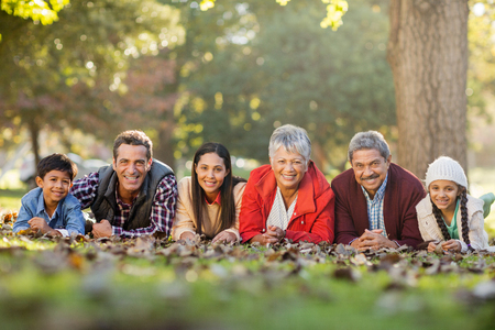 Portrait of happy family lying on front against trees at park
