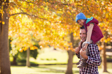 shoulder carrying: Portrait of father carrying son on shoulder against autumn trees at park Stock Photo