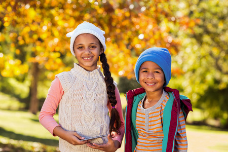 siblings: Portrait of happy siblings standing against autumn trees at park Stock Photo