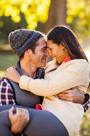 man carrying woman: Romantic man carrying woman at park