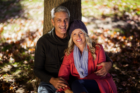 High angle portrait of couple sitting under tree at park