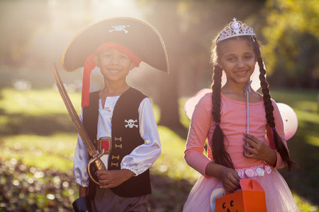 mujer pirata: Portrait of happy siblings wearing costumes at park on sunny day