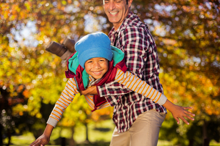 Playful father holding son at park during autumn
