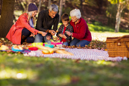 multigeneration: Multi-generation family holding autumn leaves at park