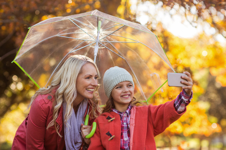 Girl taking selfie with mother while holding umbrella at park