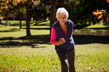personas trotando: Elderly woman making jogging in the park Foto de archivo