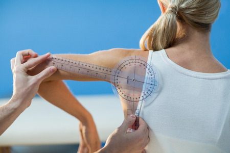 Male therapist measuring female patient shoulder with goniometer in clinic Stock Photo