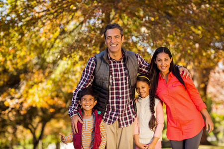 Portrait of happy family standing at park during autumn