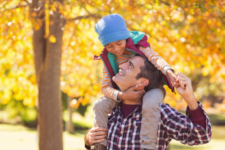 shoulder carrying: Cheerful father carrying son on shoulder at park during autumn Stock Photo