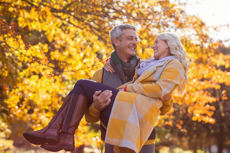 man carrying woman: Happy man carrying woman against trees at park during autumn