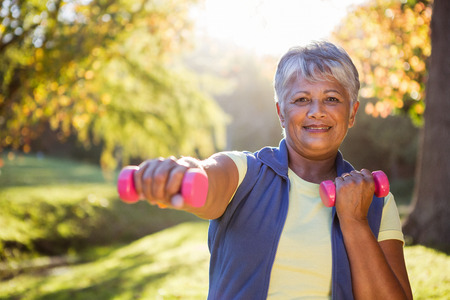 Portrait of smiling mature woman exercising with dumbbell at park