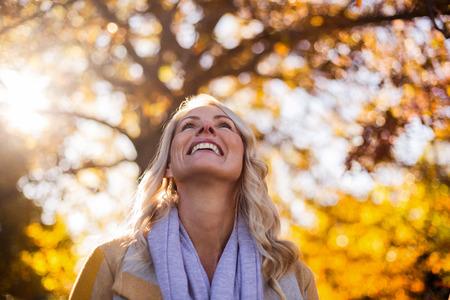 秋の間に公園で木に探している笑顔の女性