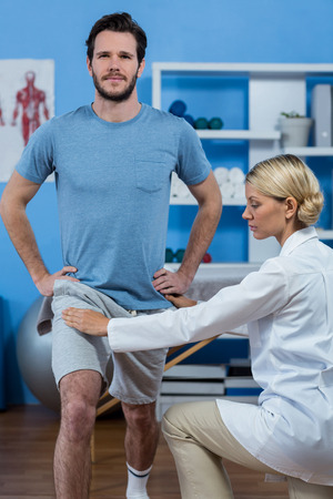 recuperation: Physiotherapist assisting patient while exercising in clinic