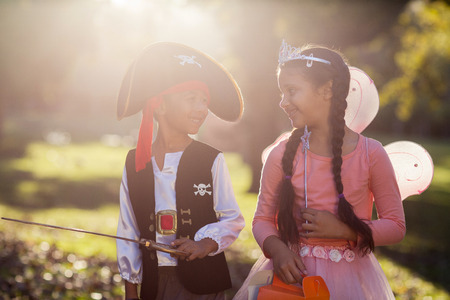 siblings: Smiling siblings wearing costumes at park on sunny day Stock Photo