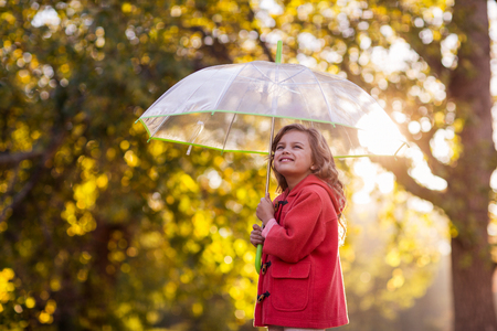 Side view of girl holding umbrella against trees at park