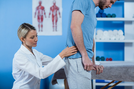recuperation: Physiotherapist examining mans back in clinic Stock Photo