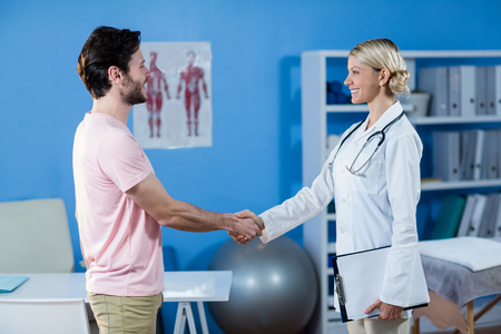 Physiotherapist shaking hands with male patient in the clinic