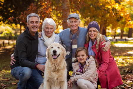 multigeneration: Portrait of multi-generation family with dog at park during autumn Stock Photo