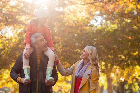 shoulder carrying: Father carrying daughter on shoulder while standing at park during autumn Stock Photo
