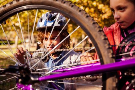 siblings: Siblings repairing mountain bike in park