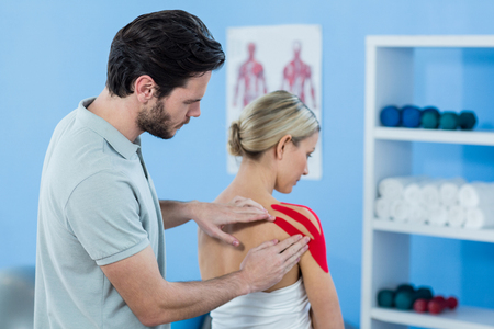 sticking to: Physiotherapist sticking tape on female patient in clinic