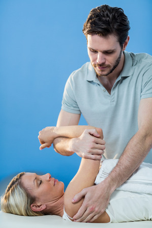recuperation: Woman receiving shoulder therapy from physiotherapist in clinic Stock Photo