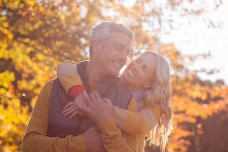 Happy romantic couple at park against trees during autumn Stock Photo