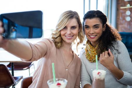 tomando refresco: Amigos femeninos sonrientes que toman una autofoto en el teléfono móvil en la cafetería Foto de archivo