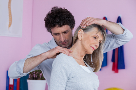 senior man on a neck pain: Physiotherapist giving neck massage to female patient in clinic