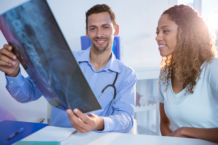 explaining: Physiotherapist explaining x-ray to patient in clinic